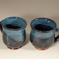 These wheel thrown pottery coffee mugs are made from a red stoneware clay and coated in a blue glaze with brown and black highlights. Each one  holds about 12 fl oz, fitting nicely in your hand.